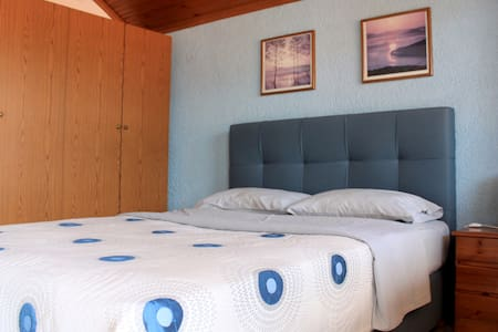 Basic apartment's bedroom with a queen size double bed and wardrobe.