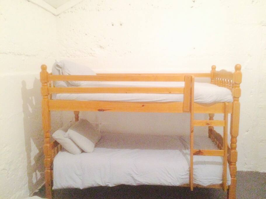 Comfortable single bed in shared dorm room.