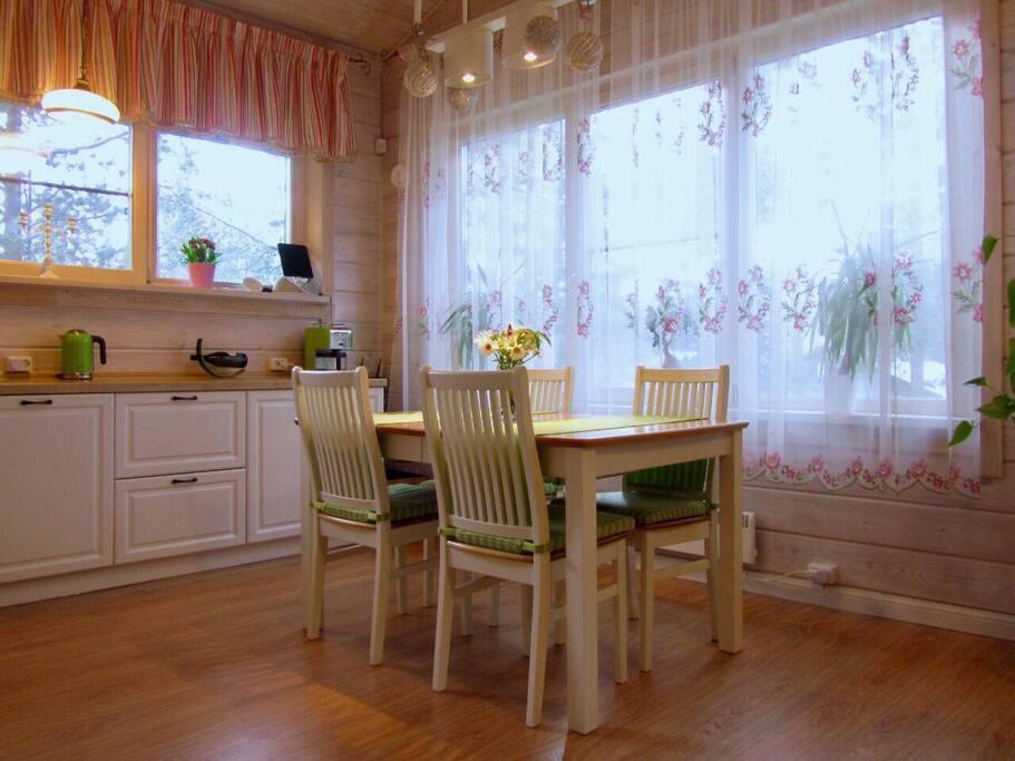 Светлая кухня большого дома с обеденной зоной