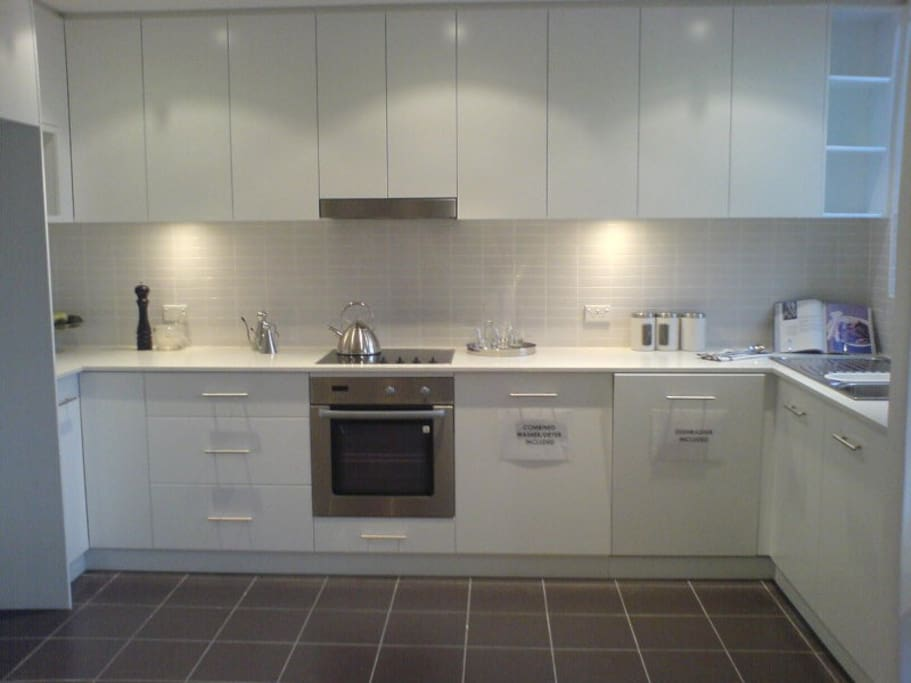 beautiful bright kitchen with dishwasher, washing machine, microwave, big fridge