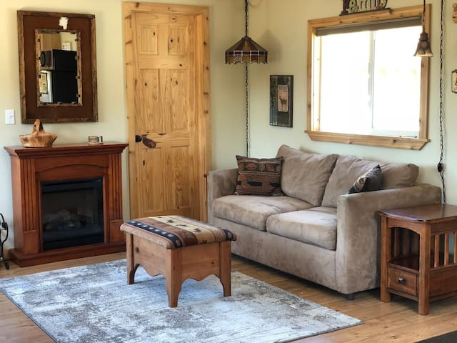 Main cabin has a full size sofa sleeper, electric fireplace, and 3/4 bath.
