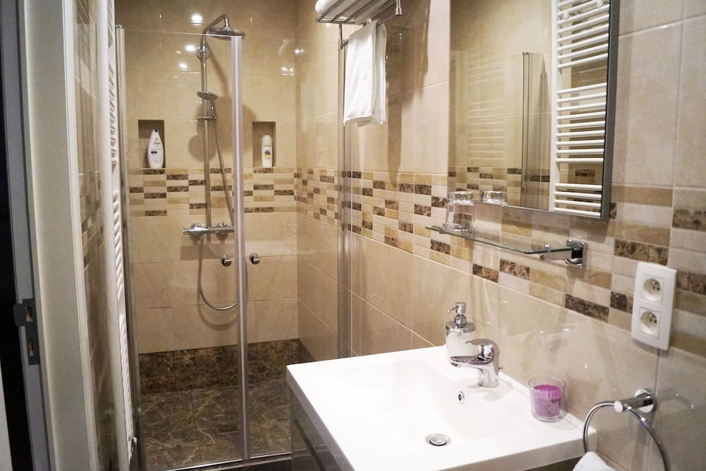 Waterfall walk-in shower with towels and brand-name toiletries.