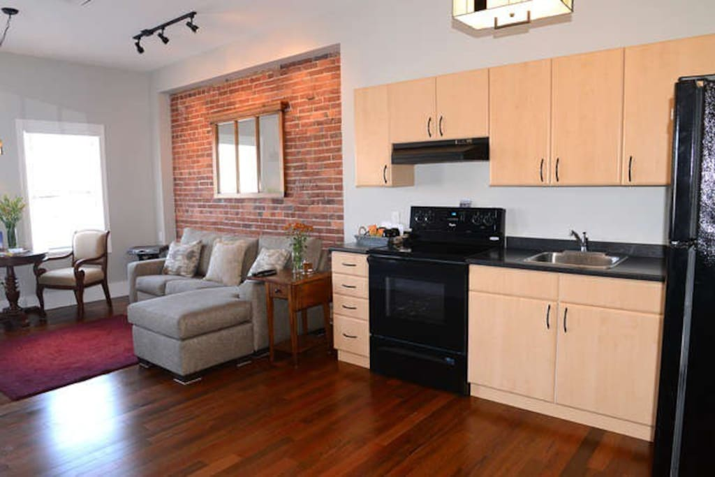 Great Room and Kitchen with an exposed red brick wall which at one te was the exterior wall of the building next door built in the late 1800's. Kingston has an amazing amount of old brick and stone buildings giving the city so much charm and character. It