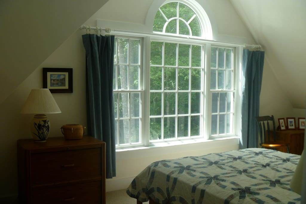 The bedroom has a view of the pond.  Insulated curtains provide darkness for sleeping, with sunny space during the day.