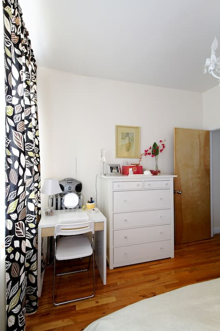 Desk and dresser at the foot of the bed.