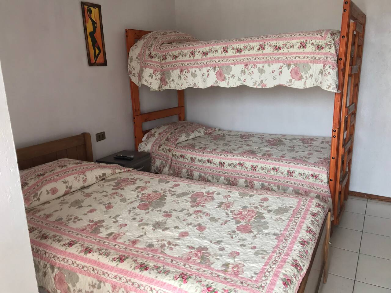 habitación con baño privada, tiene 1 cama de plaza y media y una litera.