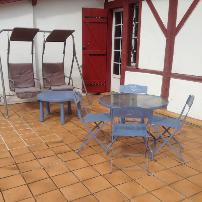 Grande terrasse carrelée avec suffisamment de tables, chaises, bains de soleil et balancelle pour votre confort .