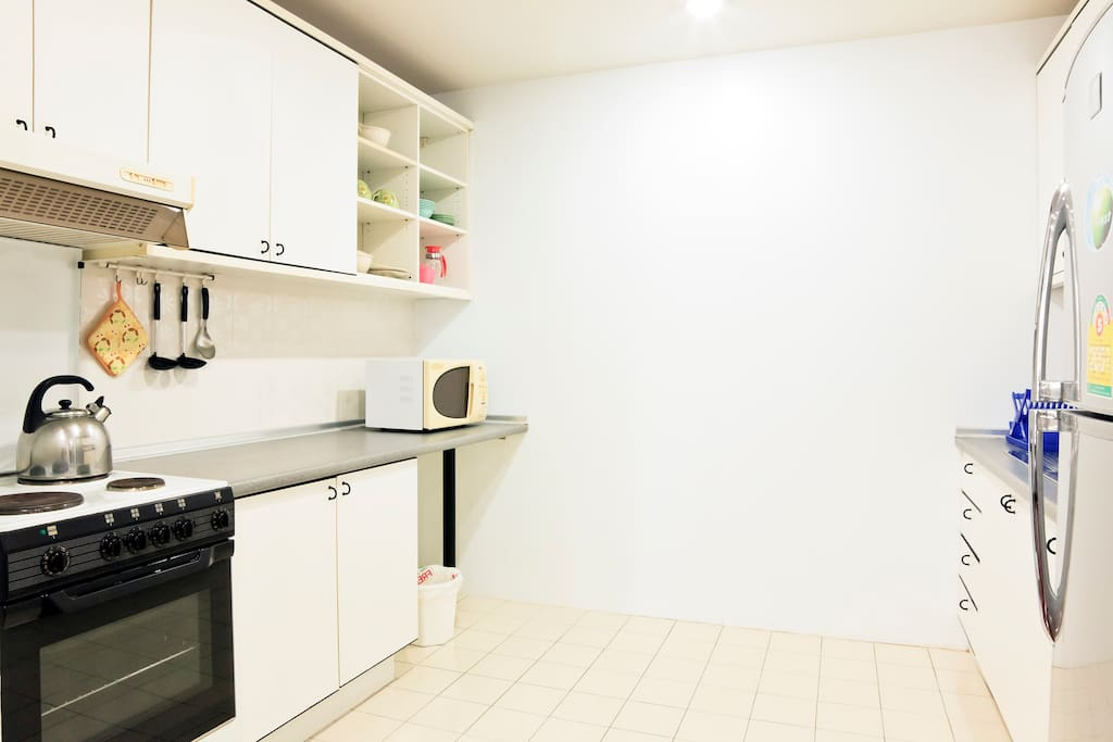 Kitchen with cookers, oven, microwave oven, refrigerator, utensils.