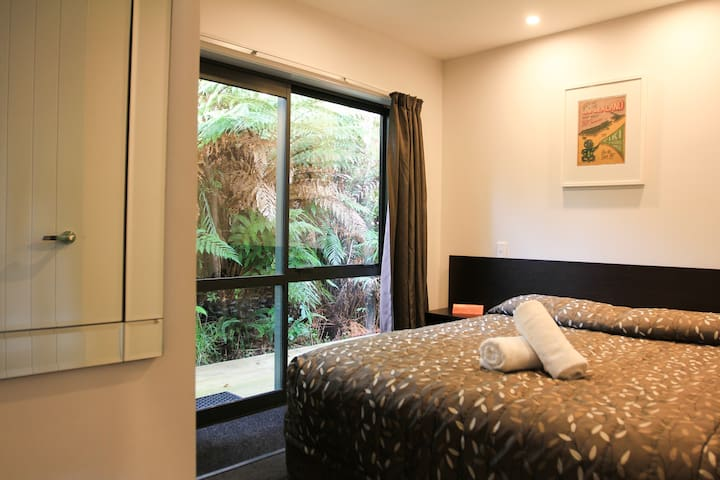 Comfortable bedroom with a queen-size bed, window walls & entrance , stylish decoration.
