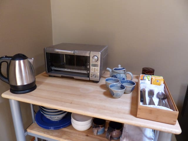 Tea kettle and selection of teas, dishes, and toaster oven