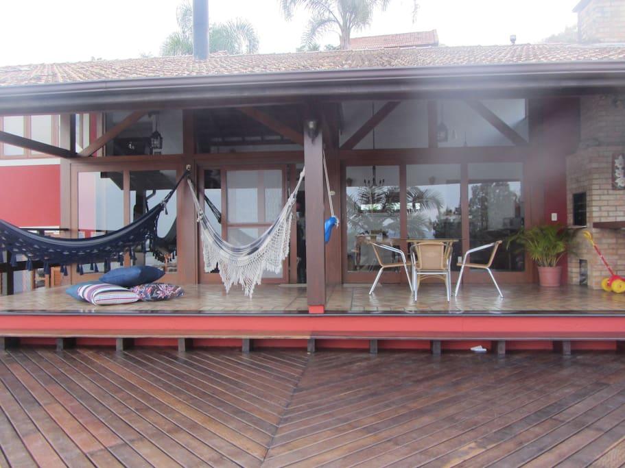 Varanda com redes, mesa, churrasqueira e forno a alenha vista do deck superior