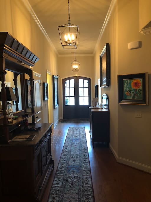 Grand entry with 13 foot ceilings. Half bath located off entry.  Original artwork in every room of the house. Antiques throughout the home as well.