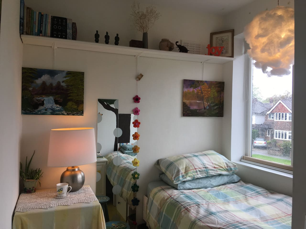 Calm arty single bedroom with original oilpaintings, soft lamp, shelf, desk, stool, drawers, mirror, radiator, books and aloe vera (helpful for sleep)