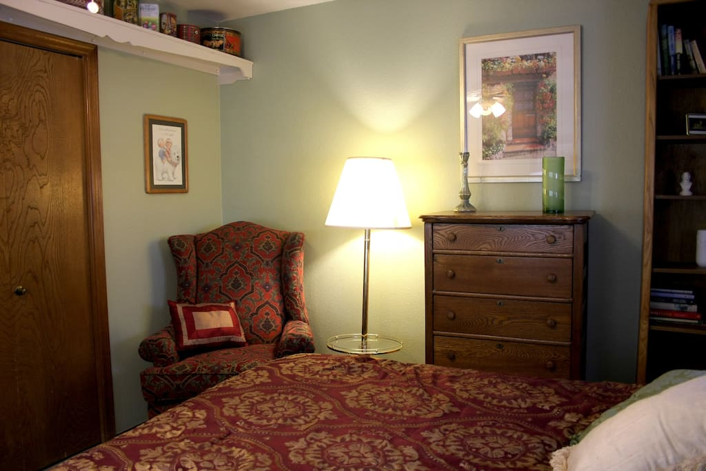 Guest room looking toward oak dresser and comfortable wingback chair and lamp table.