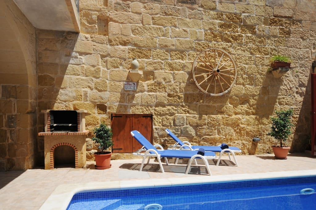 Pool area with sun loungers and stone BBQ