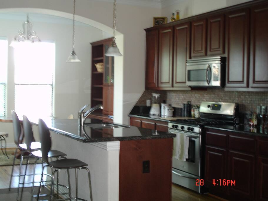 Breakfast bar, large center island, gas stove, stainless steel appliances.