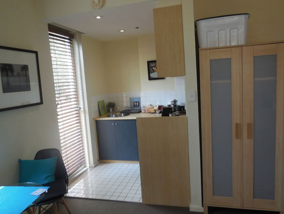 View of wardrobe and kitchenette with door to balcony