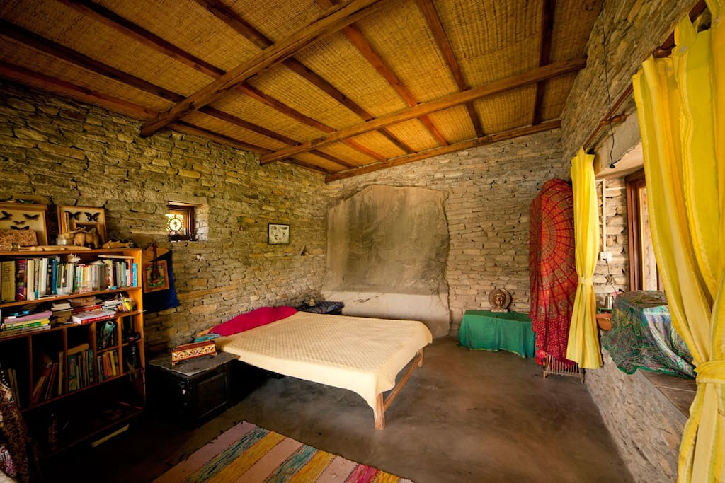 Huge bedroom built around a gigantic rock.