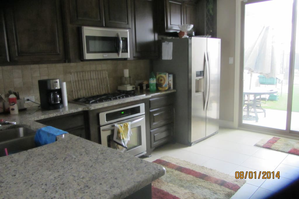 Kitchen with all new appliances with sliding door going to small backyard
