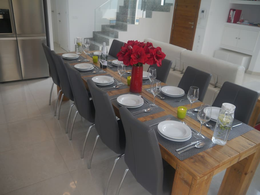The extra-long wooden dining table for 10 persons with our beautiful artificial flowers.