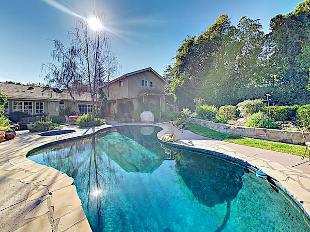 The private backyard oasis includes a sparkling pool and hot tub with plenty of space for group lounging.