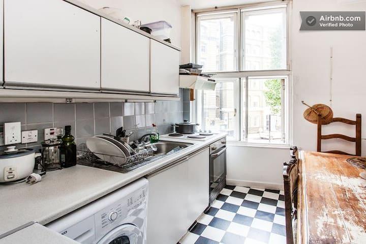 Shared kitchen with washing machine, two fridges, freezer and utensils.