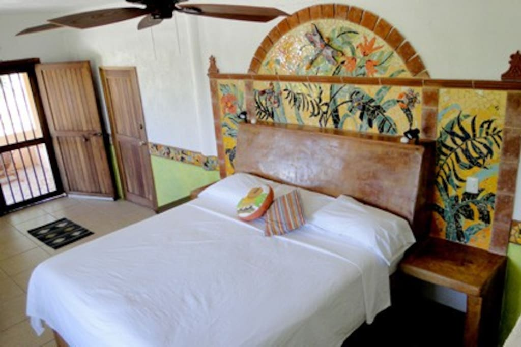 Tonina is one of our least expensive rooms and also one of the largest rooms.  It is beautifully decorated with a mosaic tiled head board. This room is Ocean view with a private patio, deck chairs and hammock.