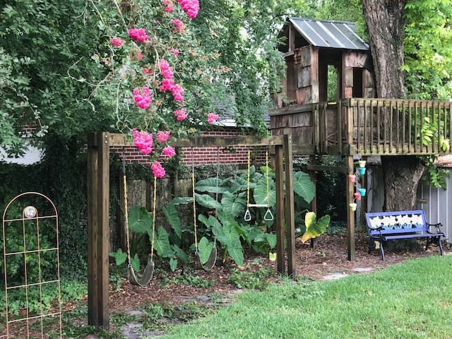Swing set and tree house in back yard