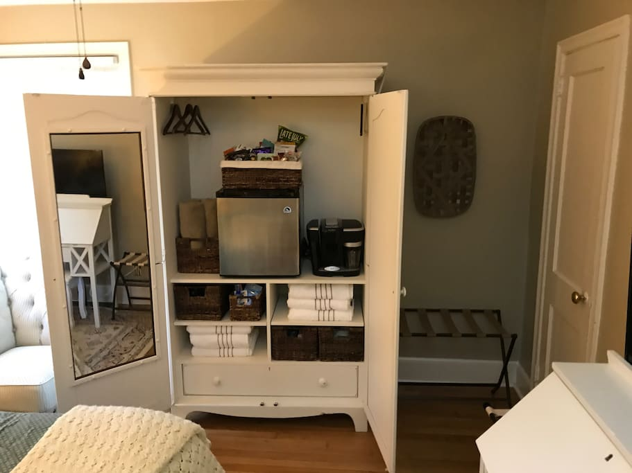 In room fridge, gourmet snacks, Lavazza espresso machine, luggage racks, and closet with hanging space and industrial-grade steamer.