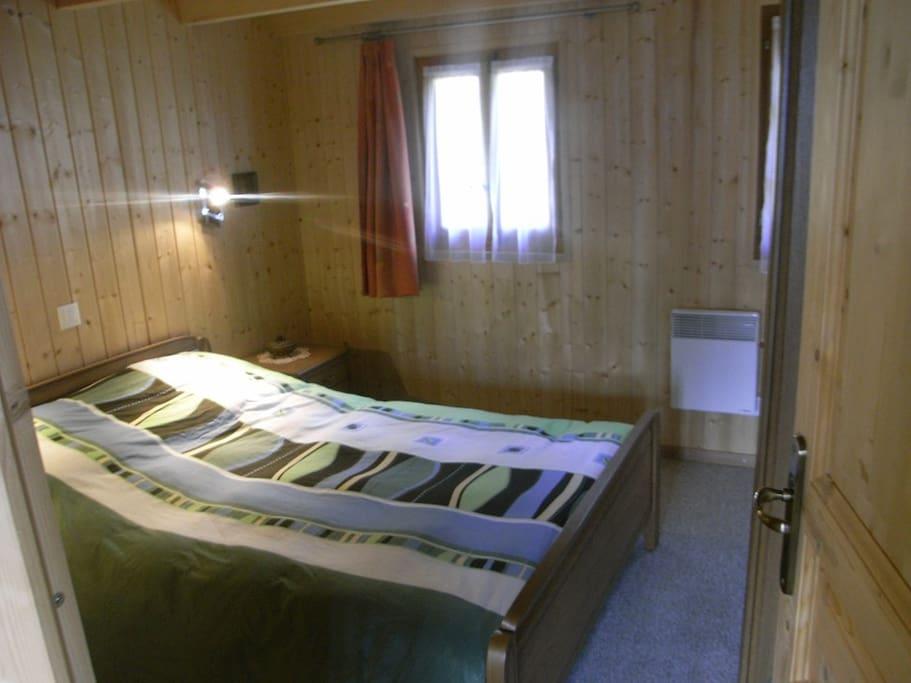 Chambre lit double avec armoire de rangement.
