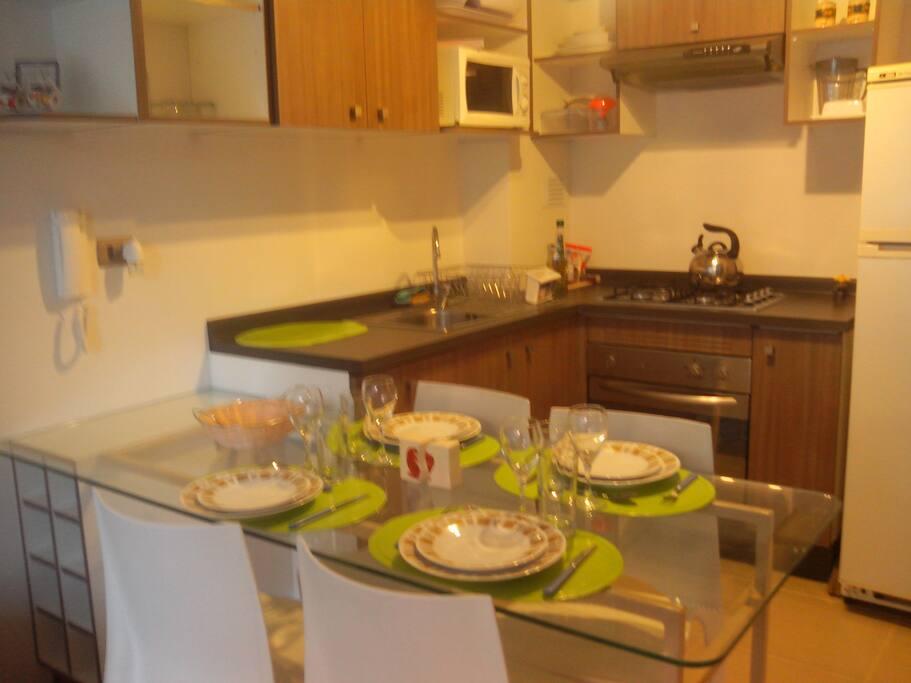 Cocina equipada con cocina a gas, horno eléctrico, horno microondas, refrigerador, baterias de cocina y vajilla completa para hasta 6 personas.