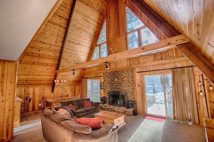 The cozy living room features comfortable couches/seating area nestled around the natural log fireplace. When sitting in these couches you can recline and rest your head and gaze upon the ponderosa tree tops and the clouds gently passing by overhead.