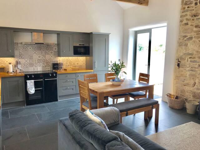 Open plan kitchen area - triple range electric fan oven, 5 ring induction hob and plate warmer; fridge freezer, washing machine