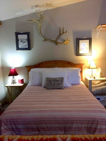 Queen Bed with a found caribou antler used as our authentic Alaska decor