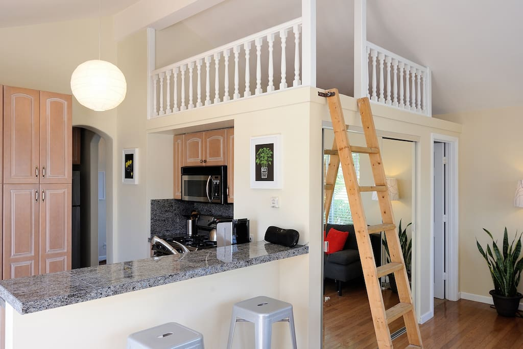 Bright, airy living space. The loft has low ceilings and a low sitting full-sized bed.