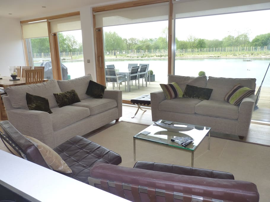 Spacious seating and dining areas with a wall of glass opening to the deck - directly over the lake.