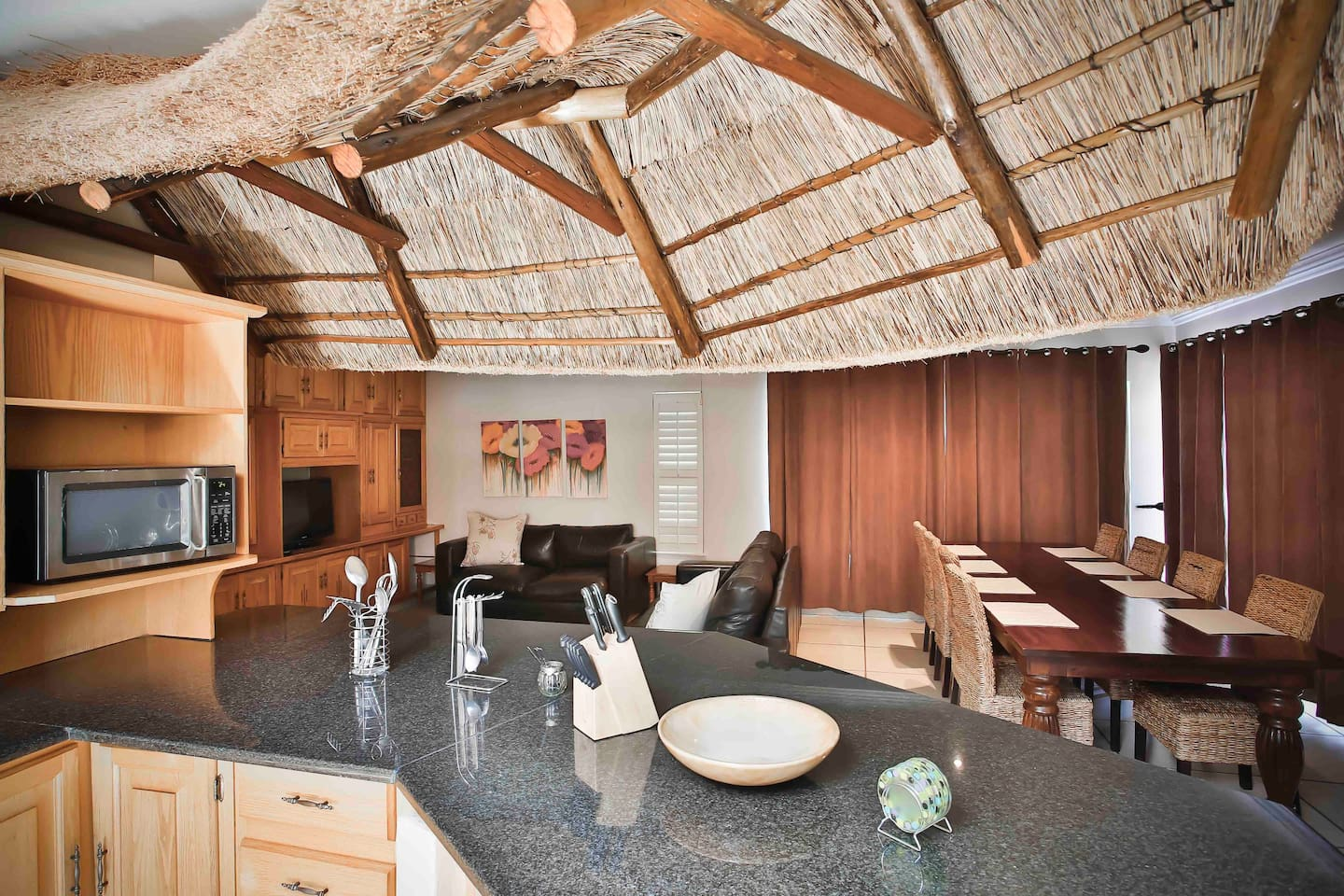 Beautiful Living area with a 8 seater dining table, leather lounge suite and a thatch kitchen counter.