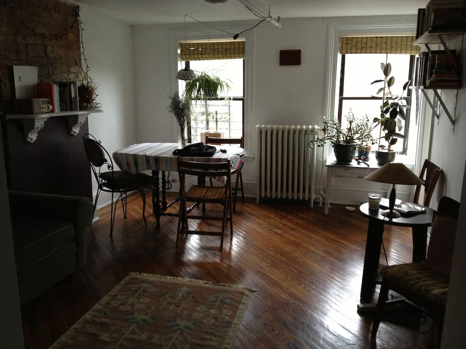 Cozy living room/dining room area- with a couch and small table for eating.