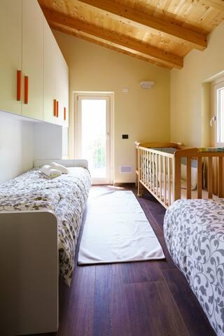 la camera con due letti singoli, la culla e il fasciatoio.