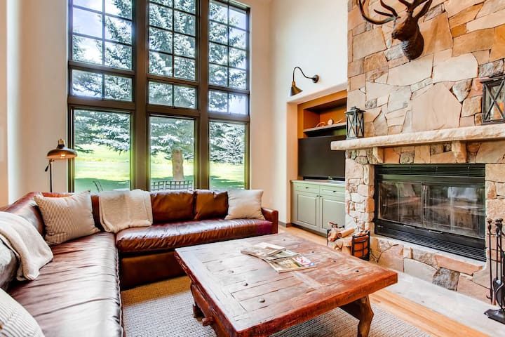 Living room with wood-burning fireplace & golf course views