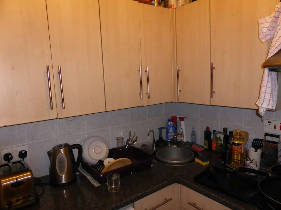Small kitchen with fridge, freezer, washing machine, oven and cooker (one hob broken).