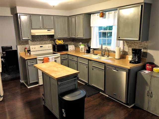 Kitchen with electric stone and oven, microwave, toaster oven, twin sinks, dishwasher, refrigerator, programmable coffee maker