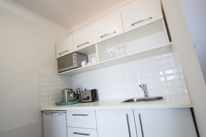 Small kitchenette with Microwave, toaster, kettle, french press, bar fridge