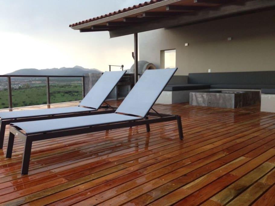 Terraza con camastros, sala cubierta con chimenea y asador, toda la terraza con espectacular vista