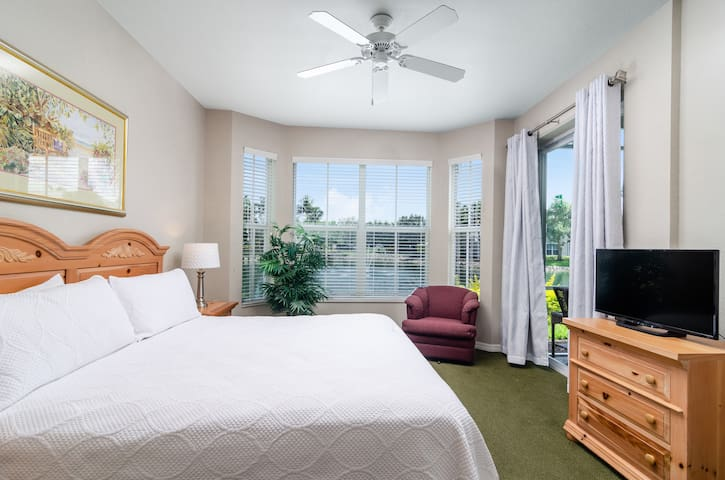 Master bedroom with king size bed, smart TV and lake view (green carpet has been replaced with new high end carpeting in a light beige color)