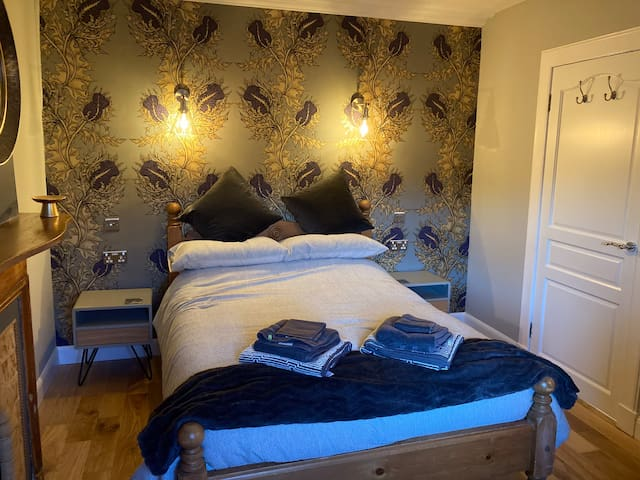 This is the main double bedroom with grey bedding. It has a brand new memory foam mattress and pillows. There are USB's and sockets by the bedside and the lighting can also be controlled from there. There is brand new hardwood floors through the property.