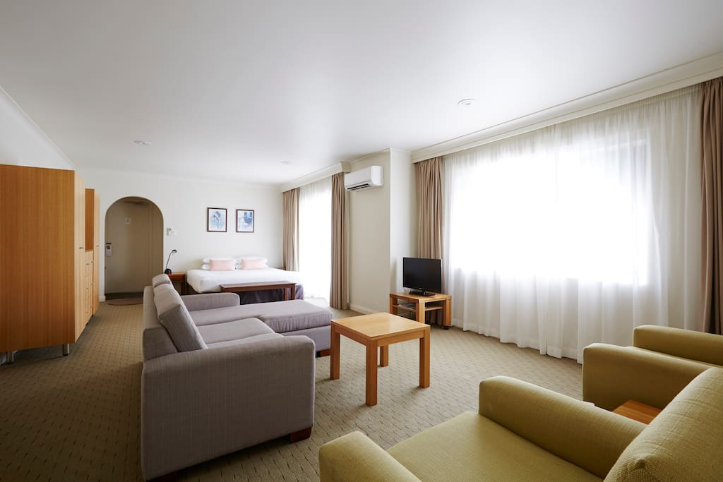 KIng size bed and lounge room with balcony and TV.