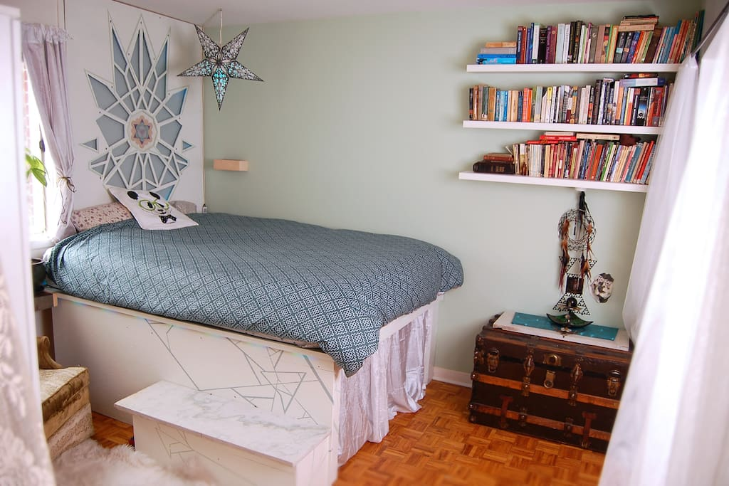 Cosy bedroom full of books and art. The headboard and edge of bed are led lined for soft, romantic lighting.