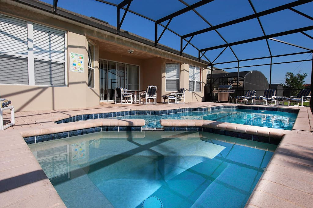 Luxurious private screened-in pool & spa with chaise loungers