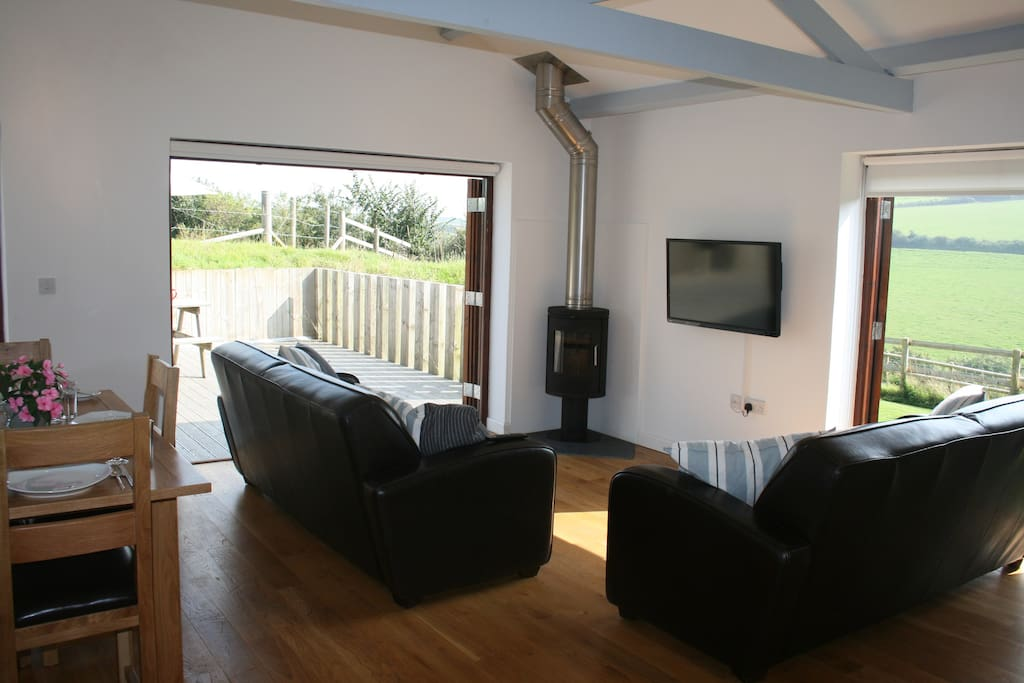 Living room with double and bi-folding doors leading to private deck and garden
